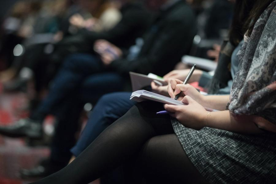 A woman sit with a pen writing in a note pad at an event. You can see others sat near her with notebooks.