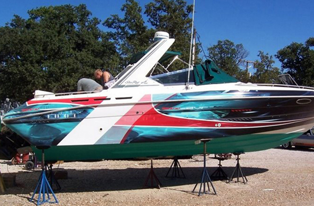 Steve Stachini BIO pic - A speed boat being wrapped in a modern multi coloured flash graphic design.