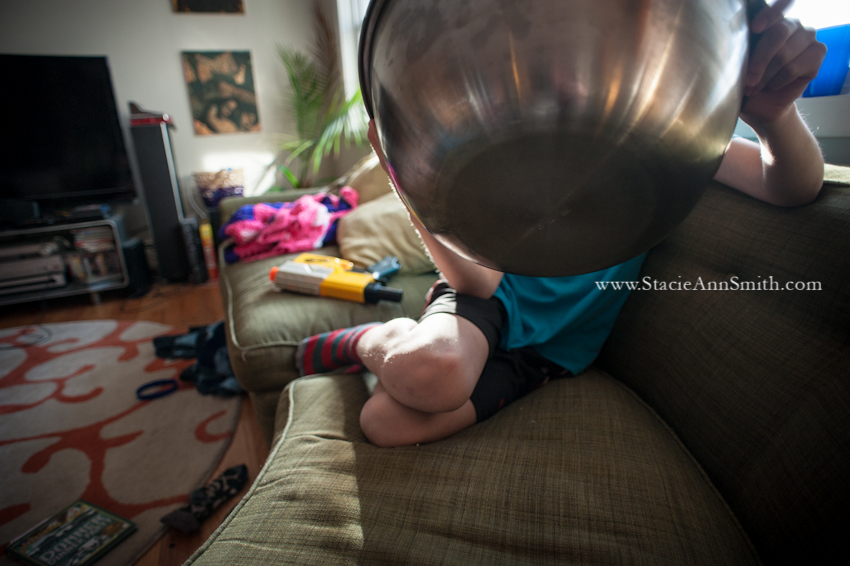 a color photograph of a child who's head is covered by the huge bowl of popcorn