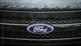 Rainy hood and grill of dark grey Ford Explorer
