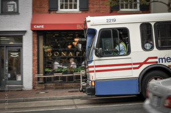 Metrobus seems to fill the entire width of Wisconsin Avenue as it travels past Bonaparte Cafe.