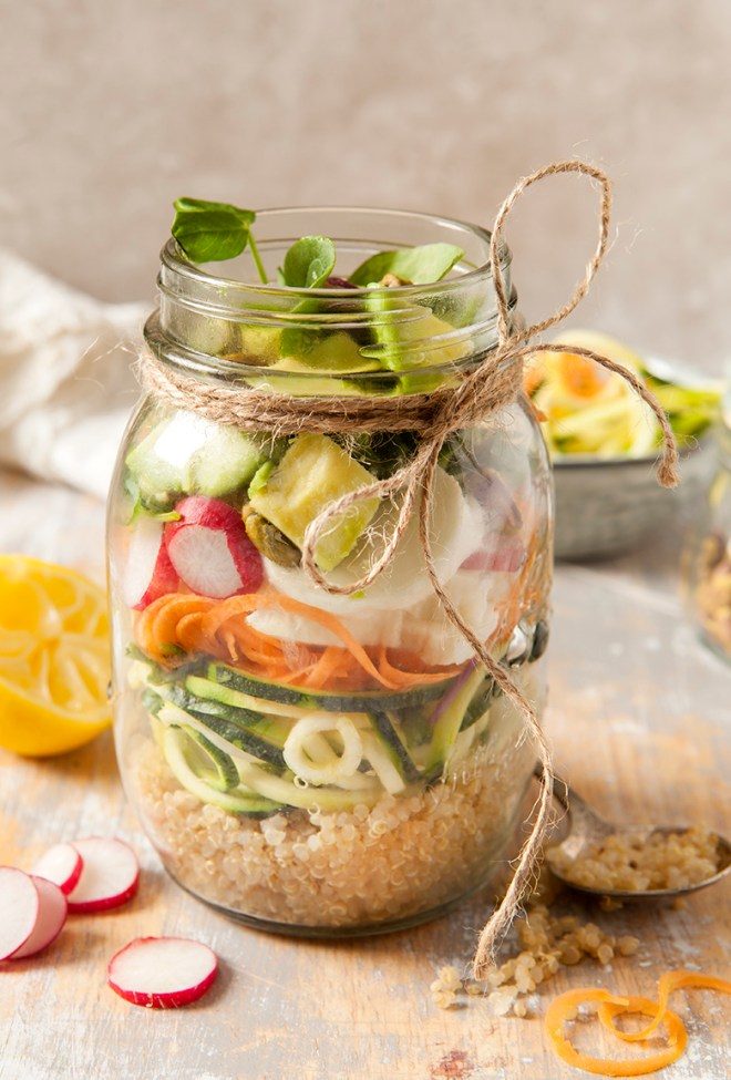 Superfood raw salad in a trendy lunch jar surrounded by the companants make it on a grey wash wooden surface and stone background