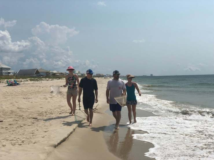 Stacy Lyn and family walking down the beach after catching crab