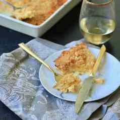 Squash casserole on a plate with fork with gray napkin under it with wine glass and casserole in background