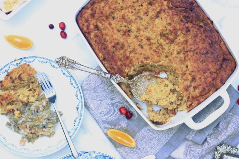 Plate with sides for Thanksgiving on the left and dressing casserole on the right in large rectangle white casserole dish