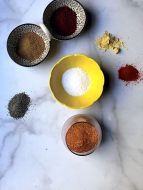 Spices in various dishes to create an all-purpose dry rub on white marble