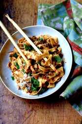 Bolognese with Venison, Wild Boar, and Beef in a white bowl on wood surface with green napkin and chop sticks