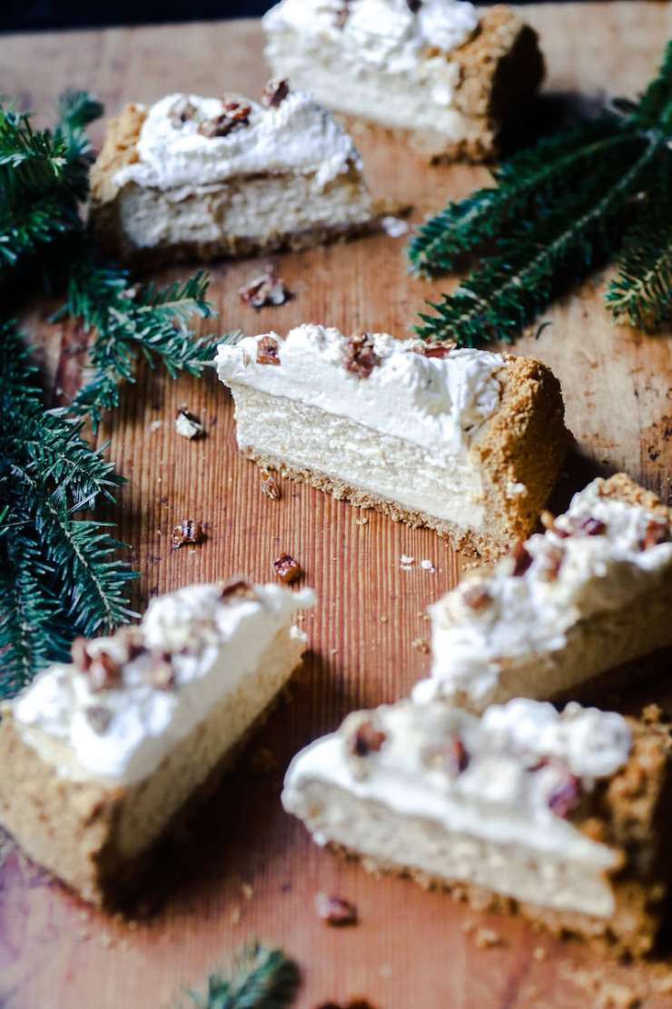 Eggnog Cheesecake with Candied Pecans placed sporadically on a board with Christmas Tree Limbs