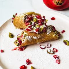 Cannoli on a pink plate with a pomegranate in the background and pomegranate and pistachios