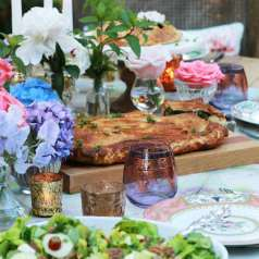 Outdoor party setting with table settings, flowers, glasses and kale pastry as centerpiece