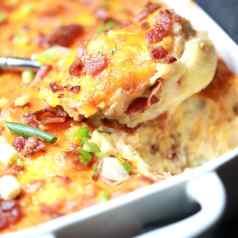 closeup spoonful of potato casserole from pan
