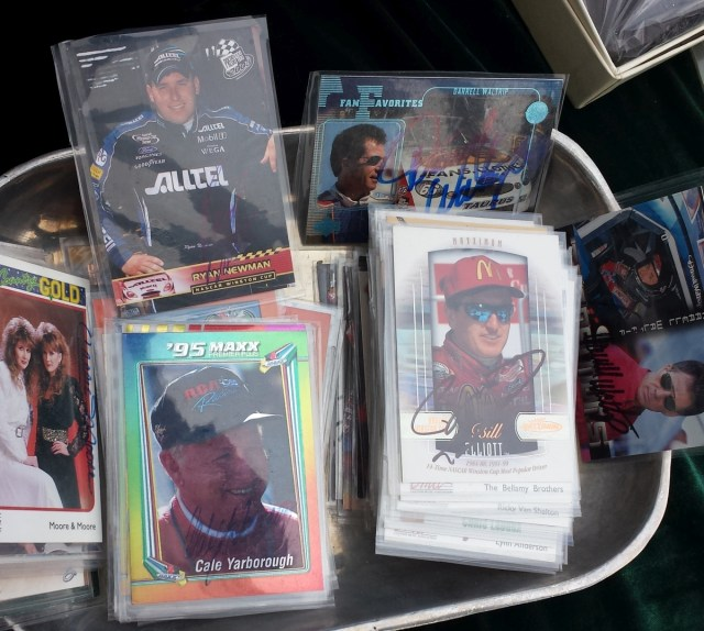 A tin full of assorted autographed NASCAR and country music cards
