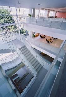 エントランスホールの上部吹抜に面して積み重なるロビー・ラウンジスペースとらせん状に連続する階段