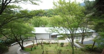 緑豊かな傾斜地に建つ宿泊研修施設:三枚の屋根が連なる外観