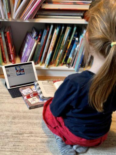 Kind von hinten, es sitzt vor den zwei Tierpolizei-Büchern und einem Tablet, auf dem die Tierpolizei als E-Audio zu sehen ist