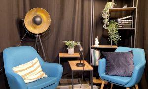 Kulisse im Social-Media-Studio. Im Vordergrund zwei hellblaue Sessel und ein Tischchen mit einem Mikrofon. Dahinter ein Regal mit Deko, ein weiteres Tischchen und eine goldene Stehlampe aus Metall. Die Raumwand dahinter wird von einem schwarzen Vorhang komplett verdeckt.