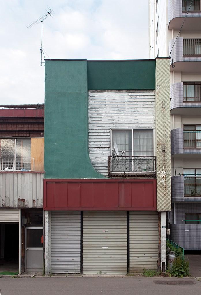Rechteckiges Haus zwischen zwei anderen Häusern
