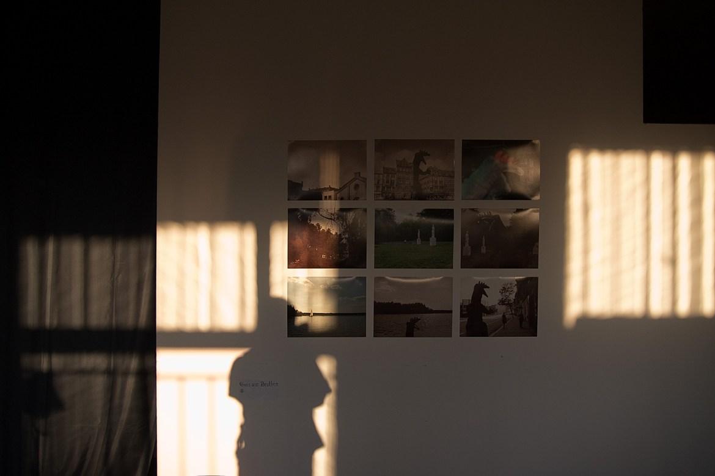 Fotografien an einer Wand die von Abendlicht beschienen wird