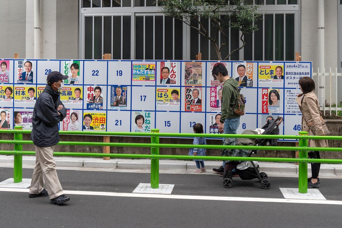 Menschen betrachten Wahlplakate bei bei den Einheitlichen Regionalwahlen in Tokio, Japan, 2019