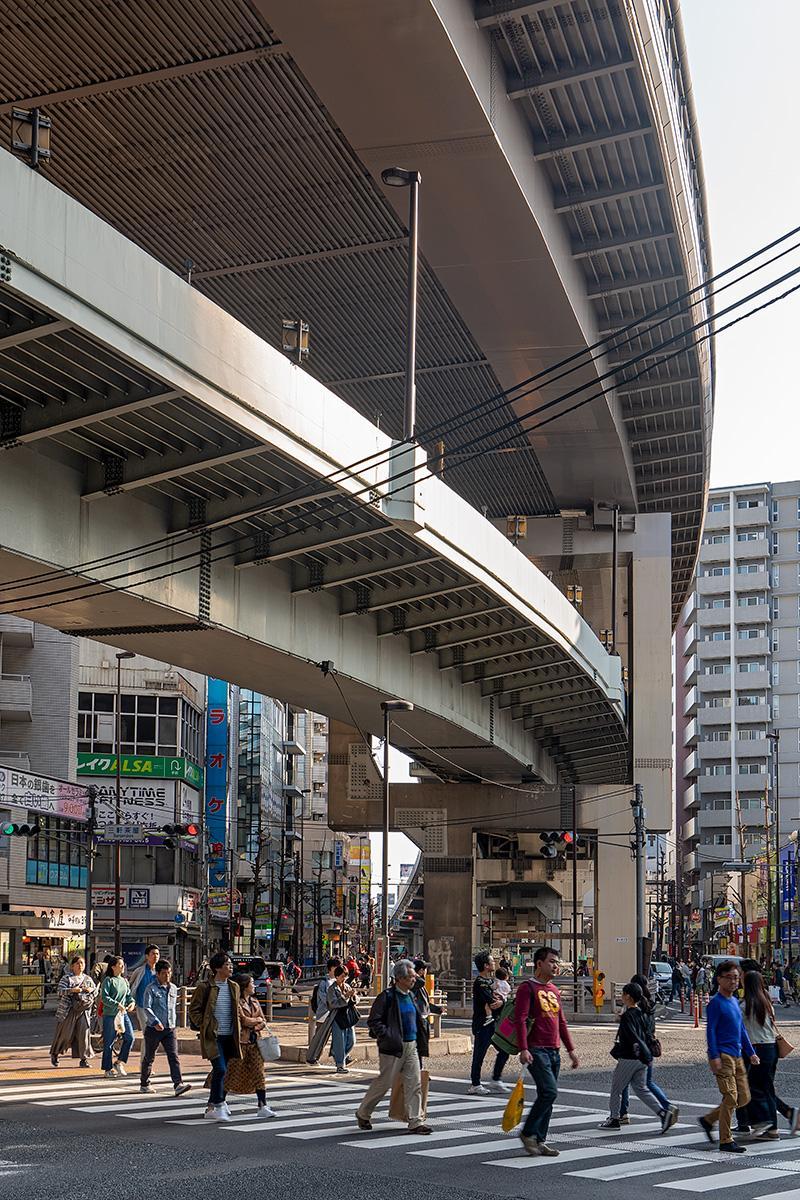Fußgänger auf Zebrastreifen unter einer Autostraße in Tokyo