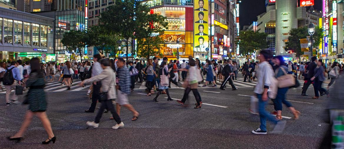 Fußgänger kreuzen die Straße am Abend in Tokyo