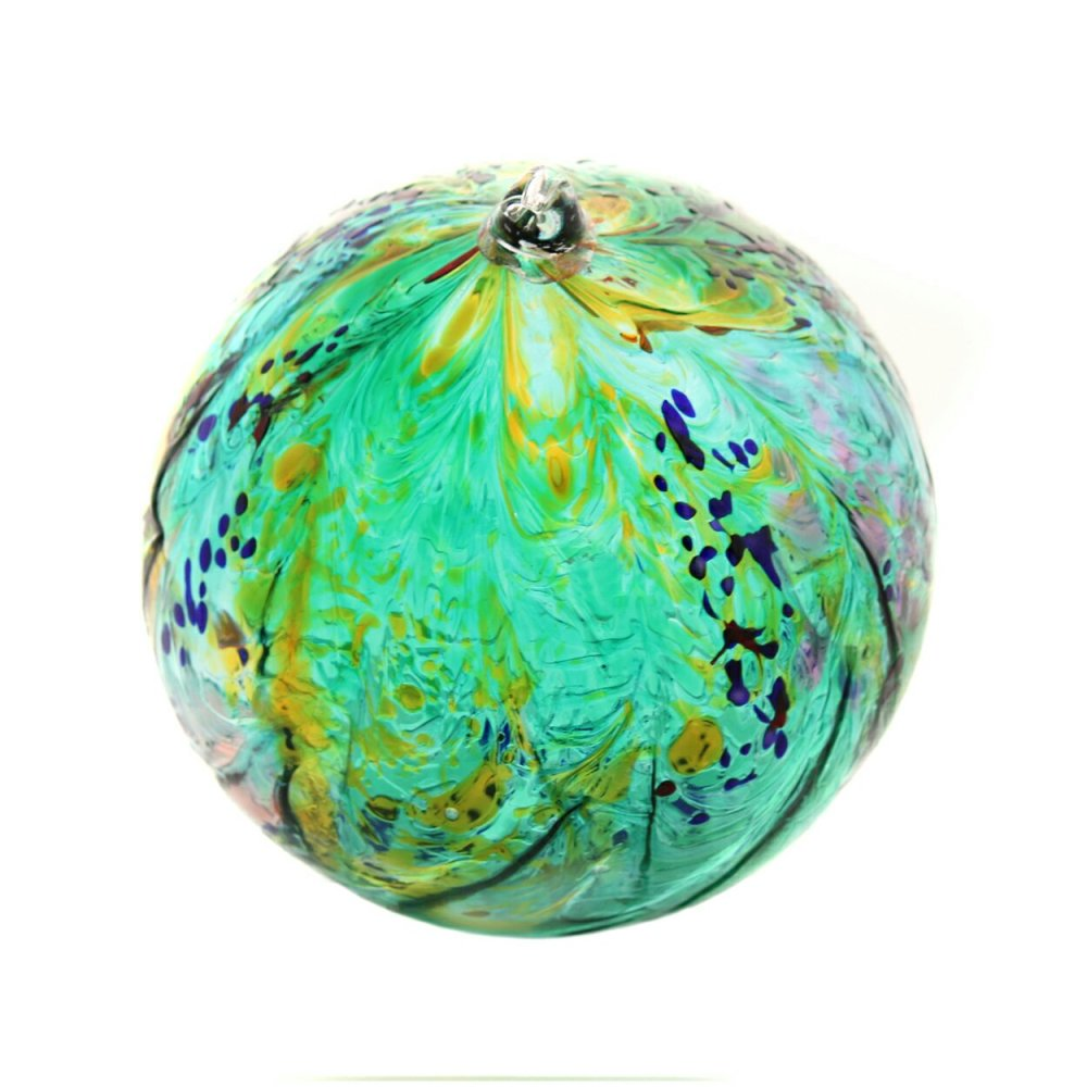 Milette's Garden is a large scale suncatcher in light green, golds, with light splashes of purples and pinks. This suncatcher is handblown and is approximately nine inches in diameter.