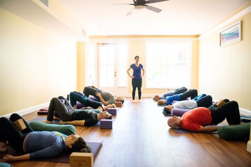 Yoga teacher stands at far end of room, between two lines of students on the floor in bridge posture.