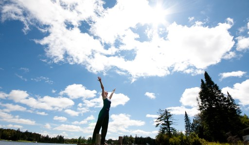 Bright blue sky with clouds lit by the sun. A woman stands in the foreground with arms raised to the sky.