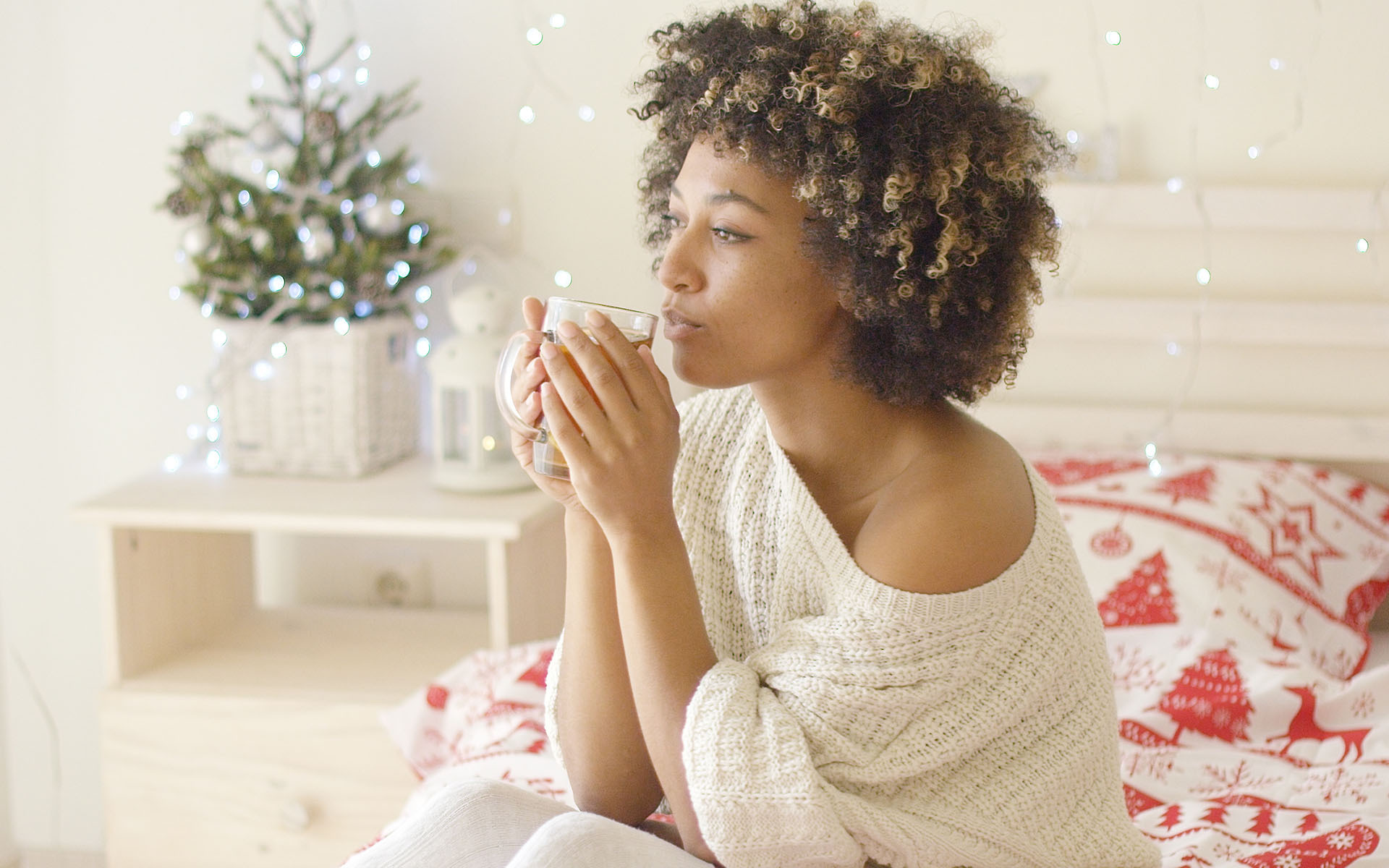 3 Ways To Find Calm in the Holiday Rush- Woman wearing white knitted sweater sips tea from mug while seated in bed. Her bedroom is white with a small Christmas tree in the corner and festive red and white bed sheets on the bed.