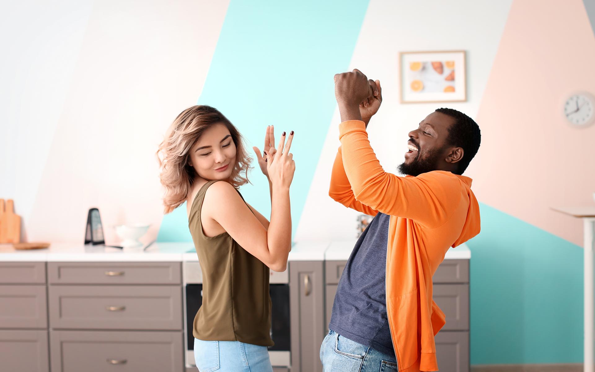 Cute interracial couple dancing at home