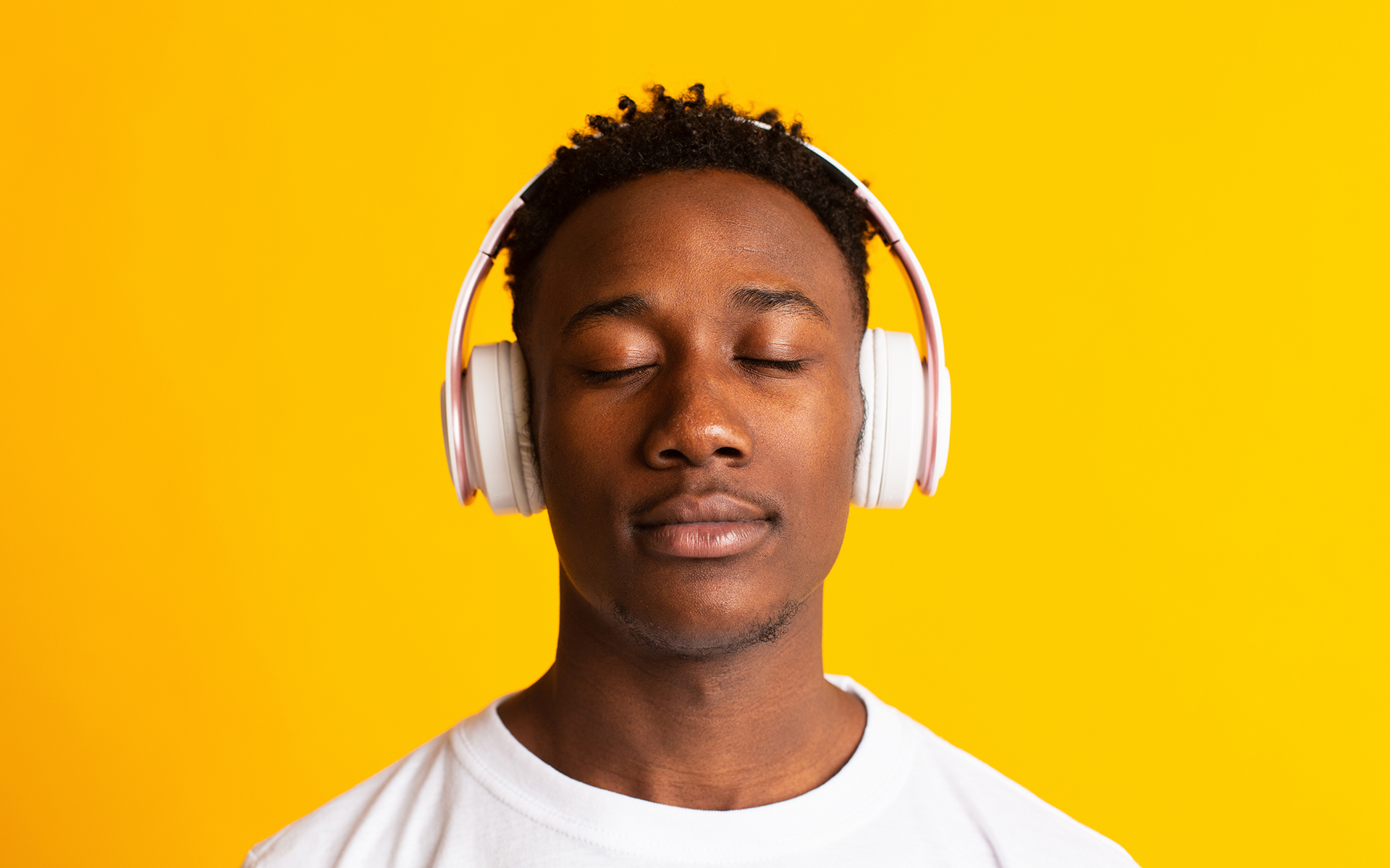 Guided Meditation for Focused Awareness - Man listening to music with headphones, closed eyes and relaxed