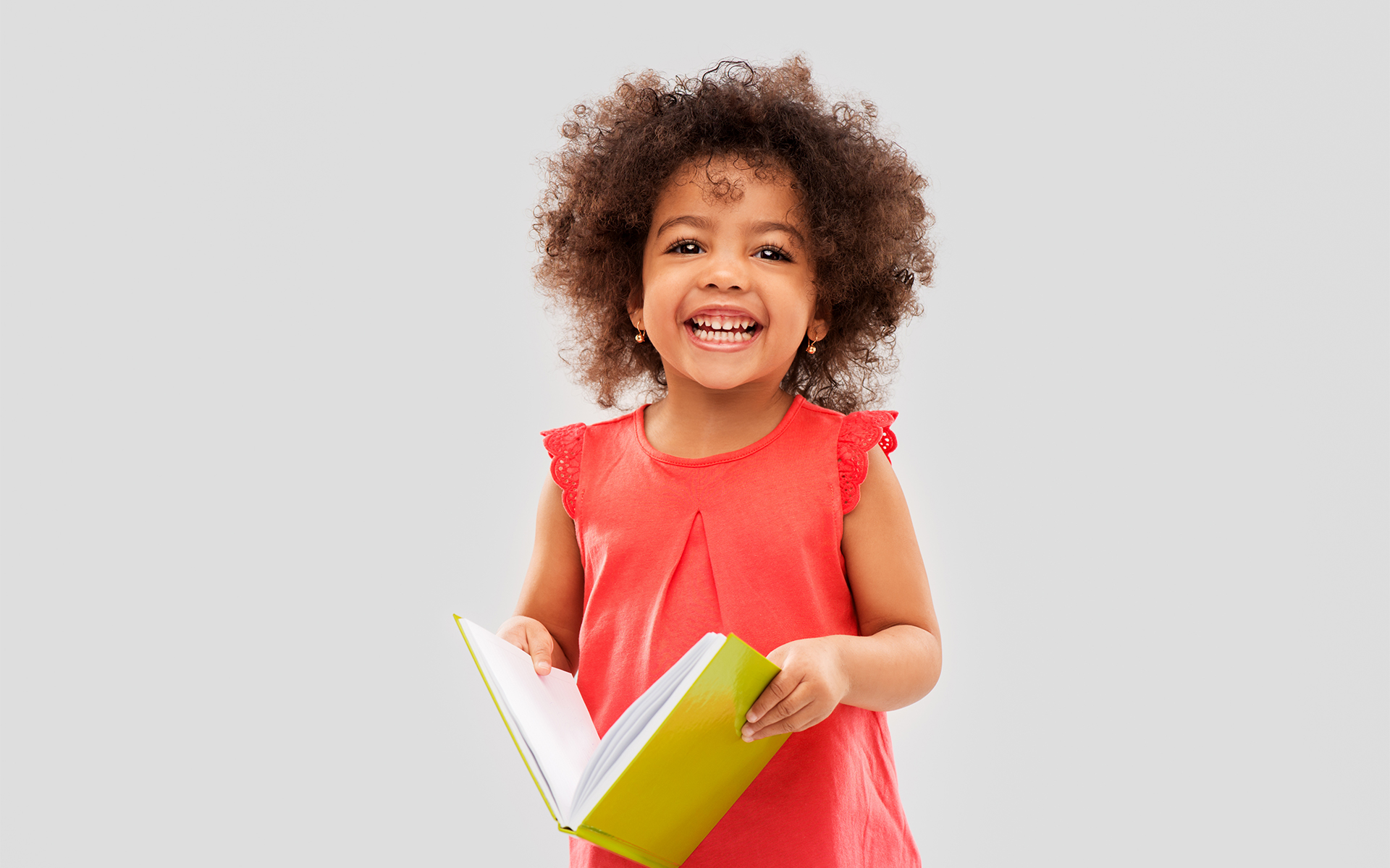 Happy young girl holding open book and smiling
