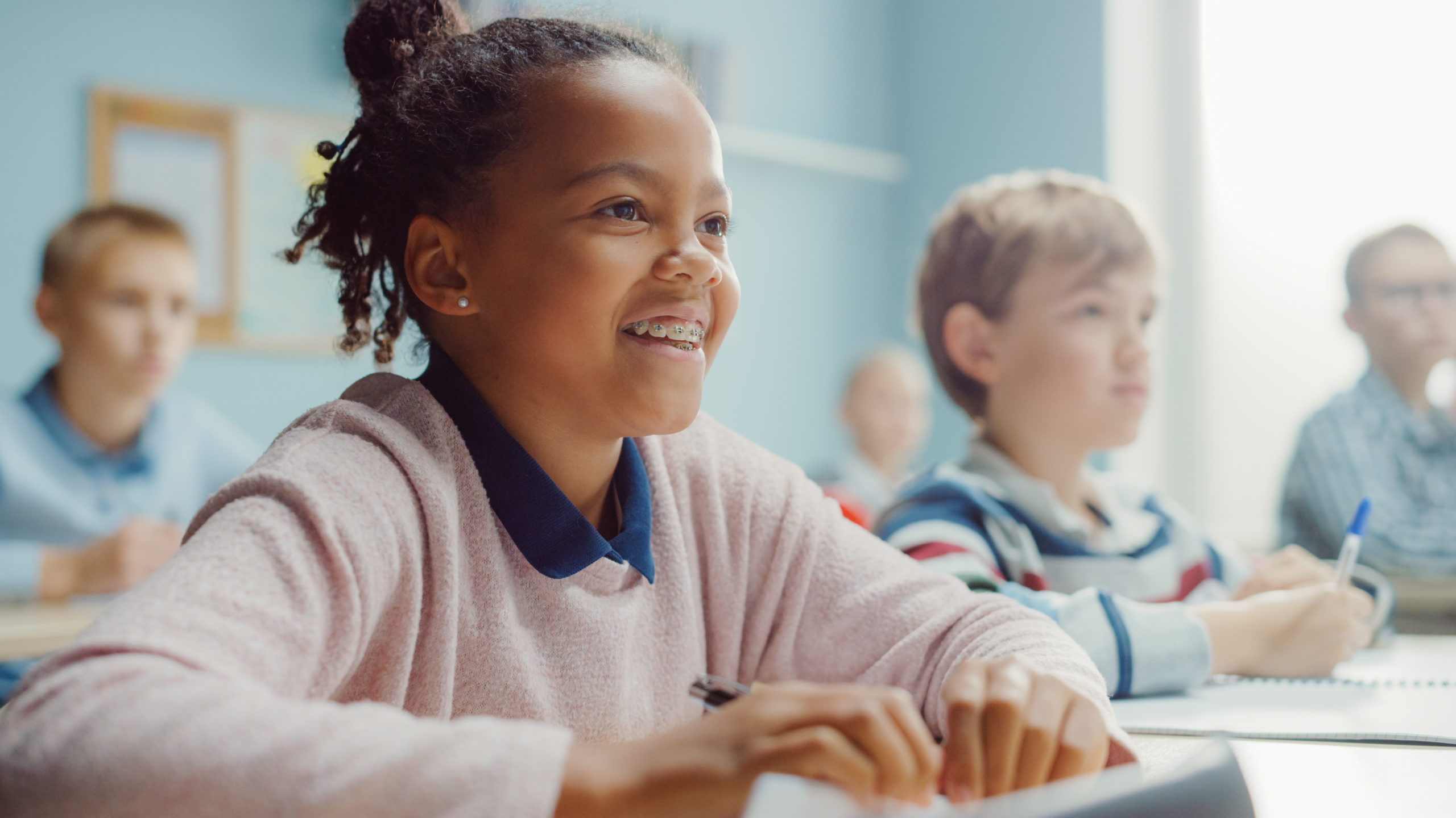 Mindfulness-Can-Empowers-Kids-Teens_child sitting in classroom with other kids smiling