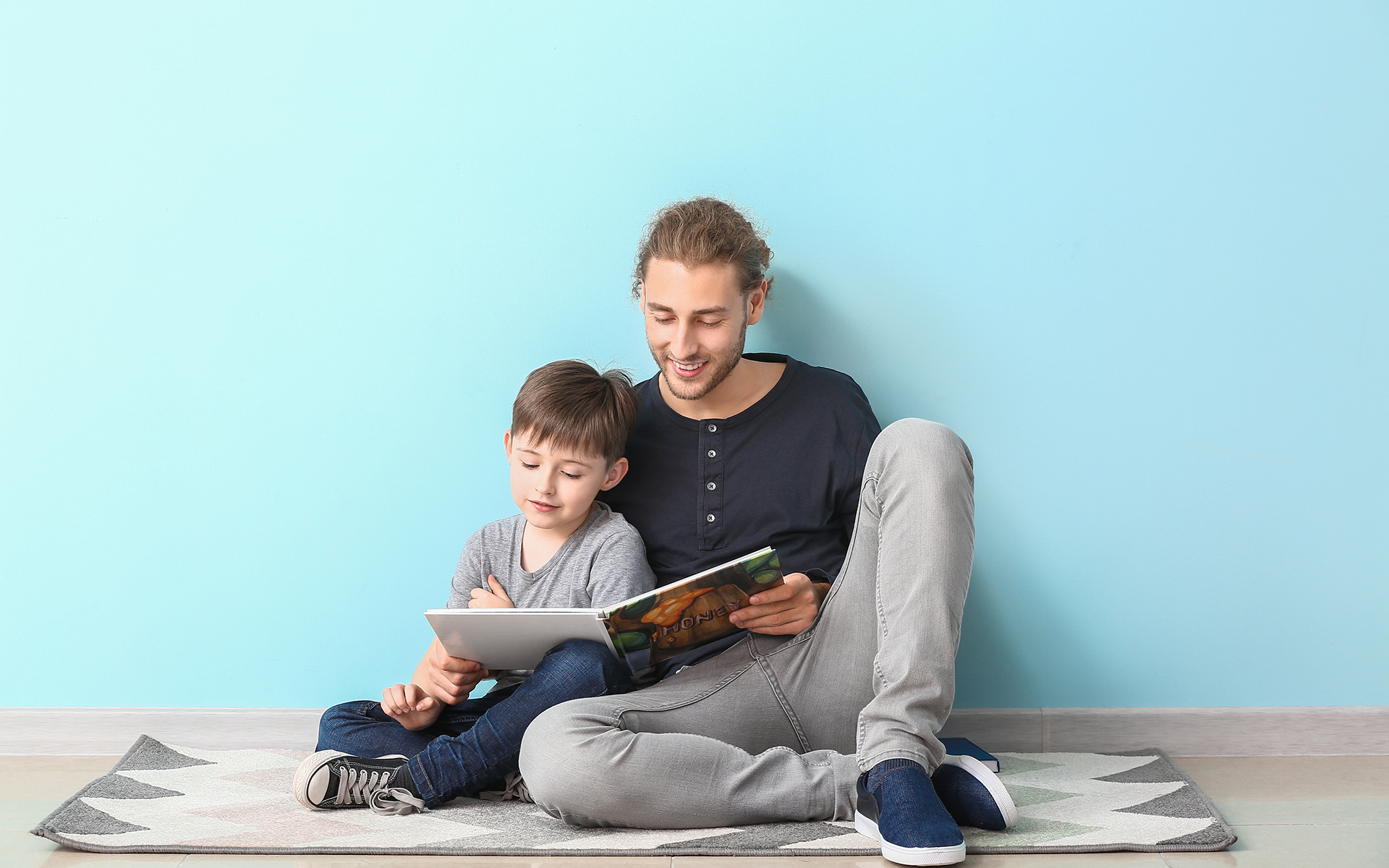 Reading Aloud: Teaching Kids About Mindfulness-father and son reading a book together sitting on the floor smiling