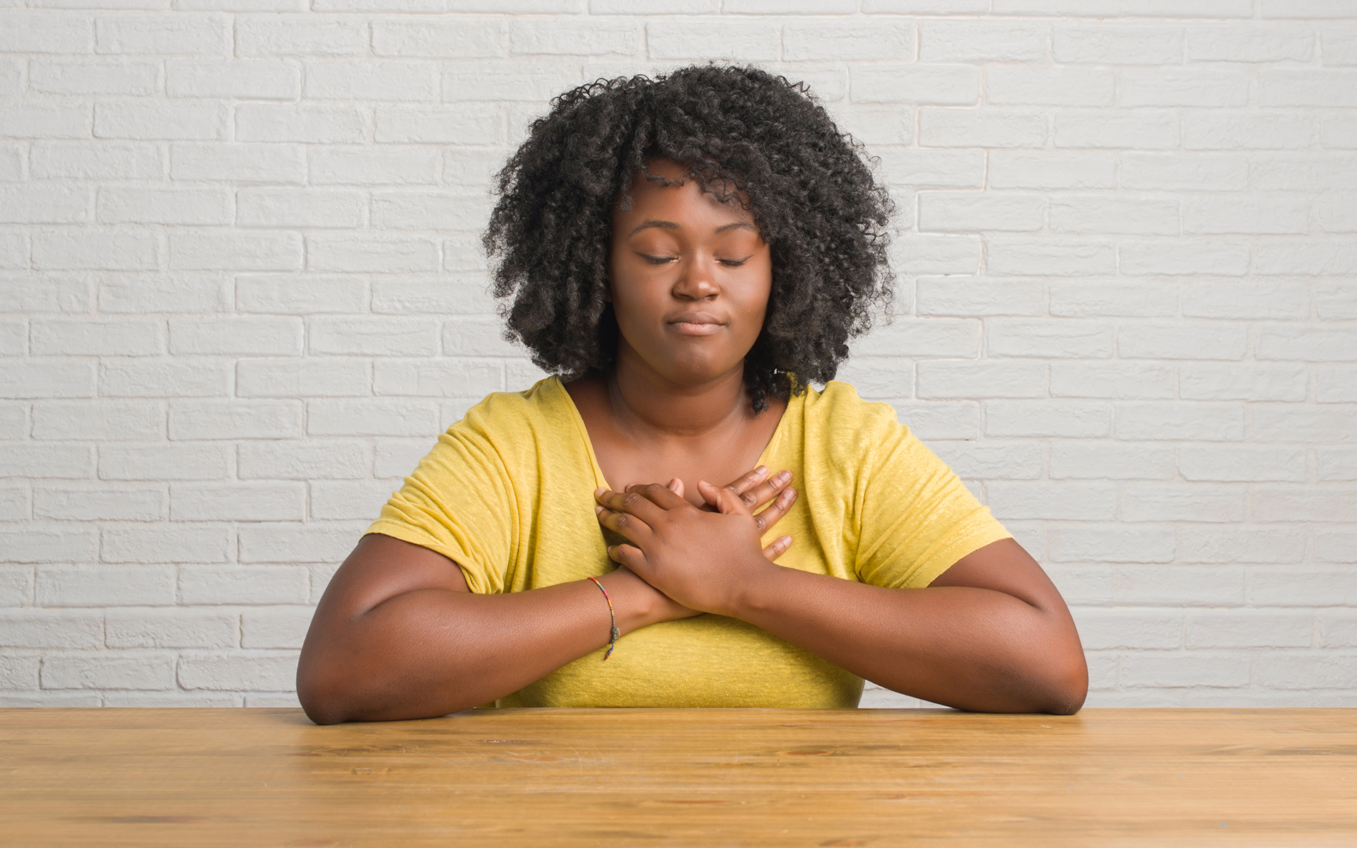 A Gentle Practice for Opening Up to Painful Emotions - Black women meditating with hands on heart