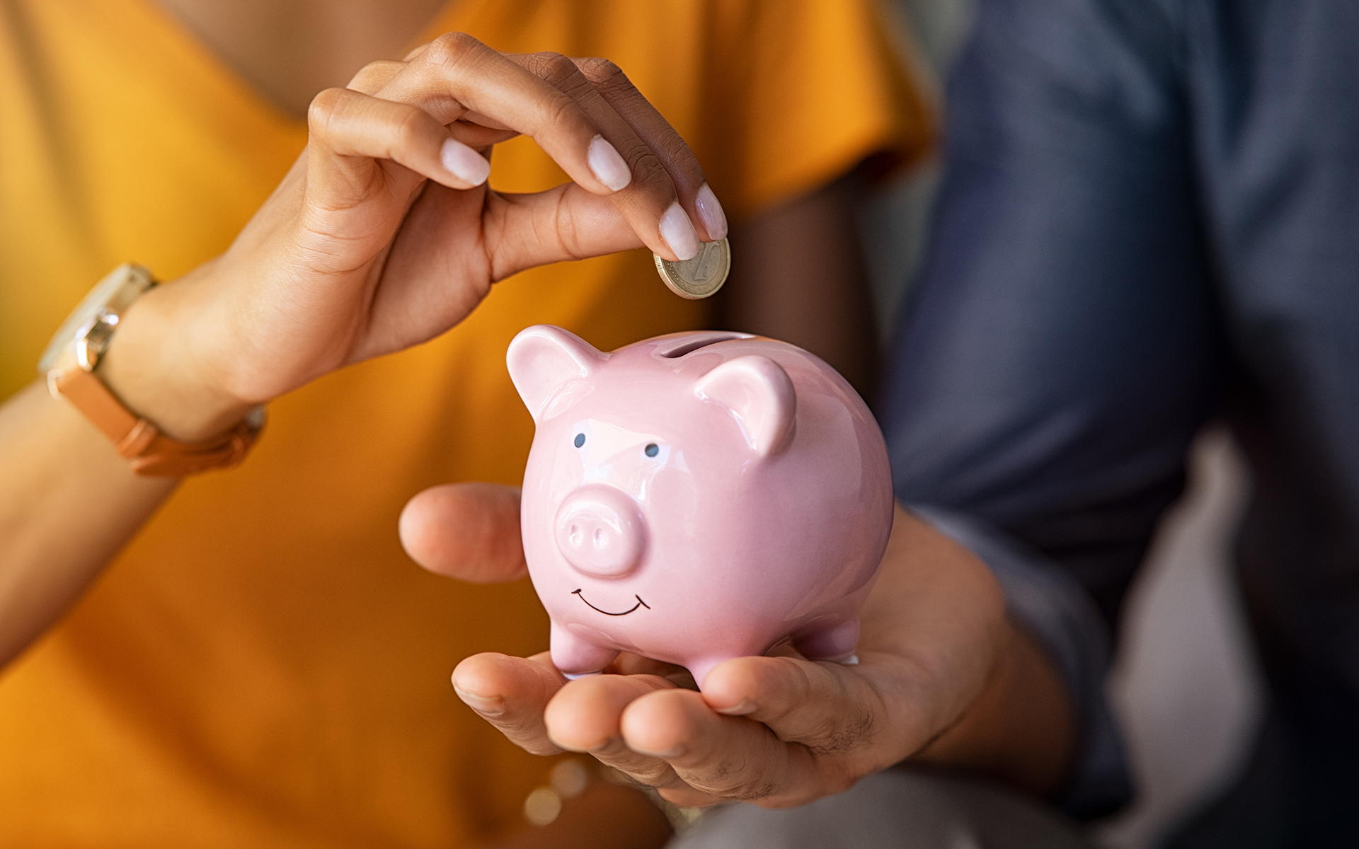 How a Money Conversation Can Transform Your Relationships- Close up of man holding pink piggybank while woman putting coin in it. Indian young couple saving money for their wedding. Close up of woman hand putting euro money in piggy bank to save for the purchase of an house.