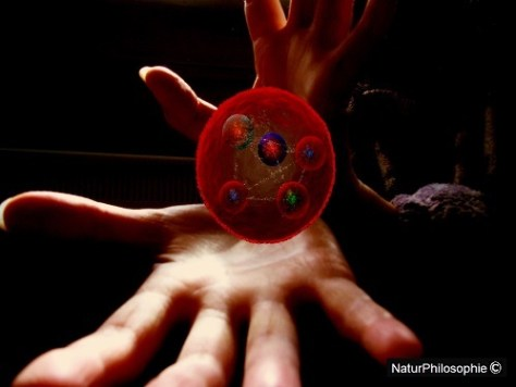 A photomontage showing my two open hands facing the camera, between which a pictorial representation in red of the elusive pentaquark particle appears to be levitating. Image: NaturPhilosophie