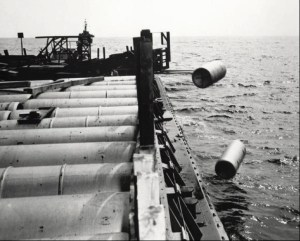 A black and white photograph showing the dumping at sea of barrels containing chemical warfare agents by the U.S. army.