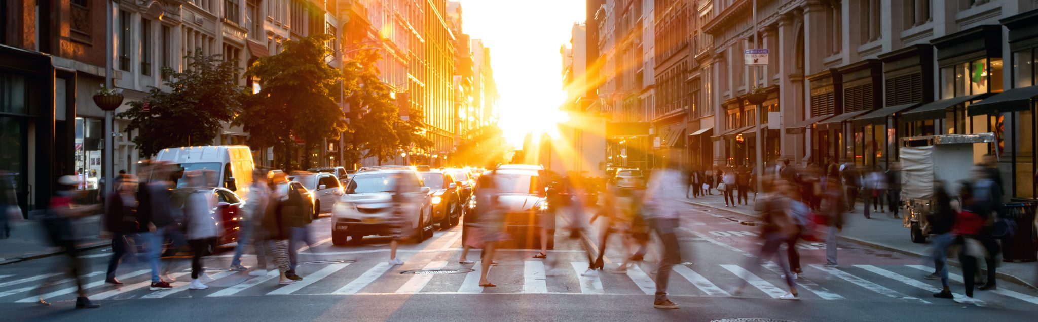 People walking in the street as the sun sets in New York City.