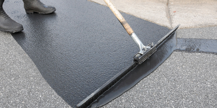 Services - Sealcoating asphalt driveway with a squeegee