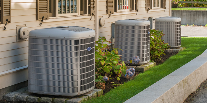 Services - Three heating/cooling units behind a set of townhouses
