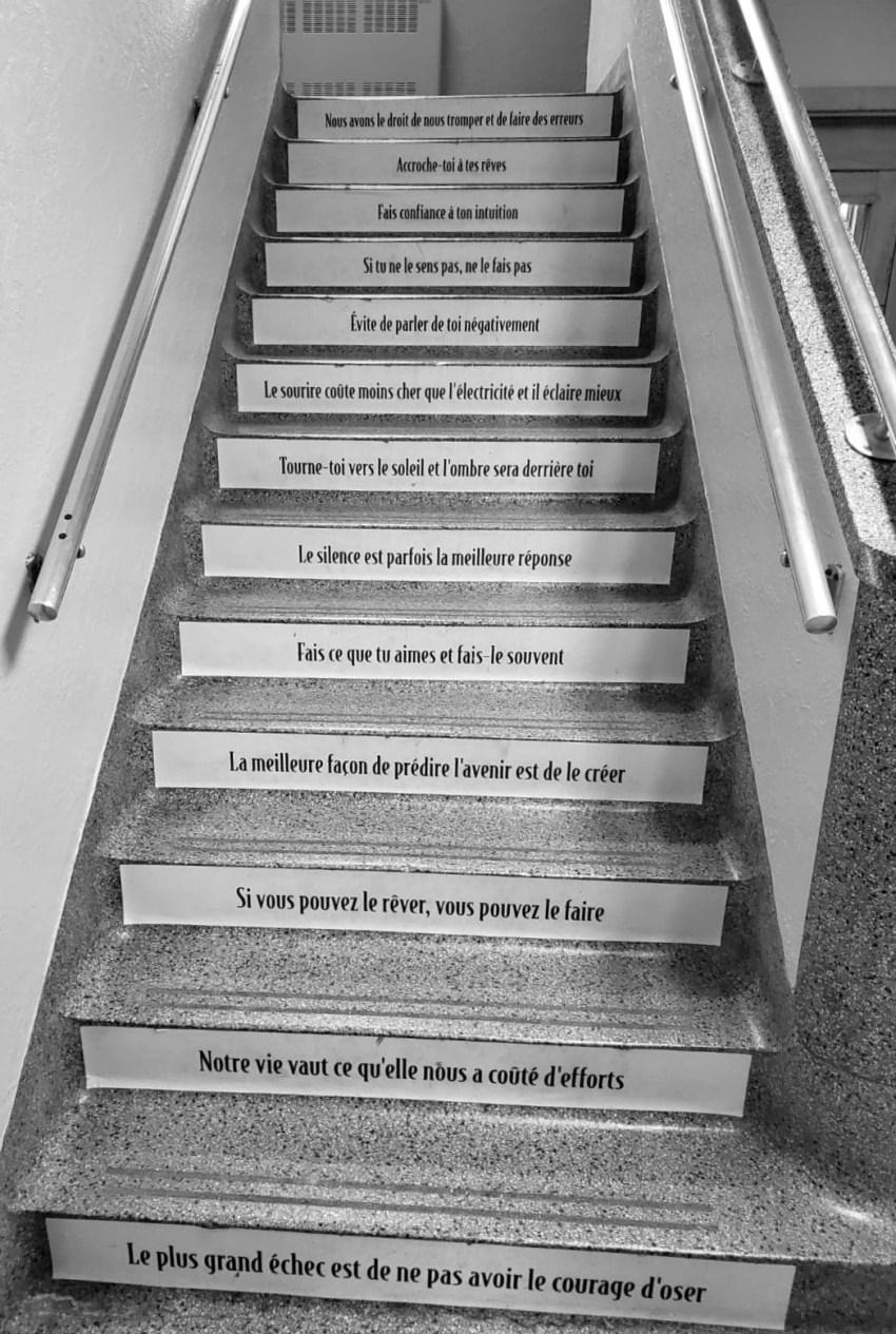 Escalier d'une école montrant des messages encourageant pour les élèves québécois
