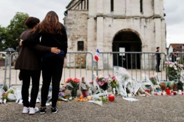 "People stand in front of a make shift memorial in front of the Saint-Etienne du Rouvray church on July 27, 2016, after the priest Jacques Hamel was killed on July 26 in his church during a hostage-taking claimed by Islamic State group. France probes an attack on a church in which two men described by the Islamic State group as its ""soldiers"" slit the throat of a priest. An elderly priest had his throat slit in a church in northern France on July 26 after two men stormed the building and took hostages. The attack in the Normandy town of Saint-Etienne-du-Rouvray came as France was still coming to terms with the Bastille Day killings in Nice claimed by the Islamic State group. / AFP / CHARLY TRIBALLEAU        (Photo credit should read CHARLY TRIBALLEAU/AFP/Getty Images)"