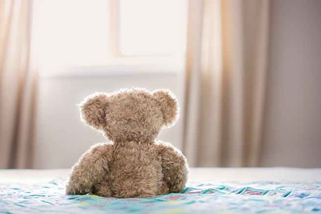 brown bear plush toy on bed