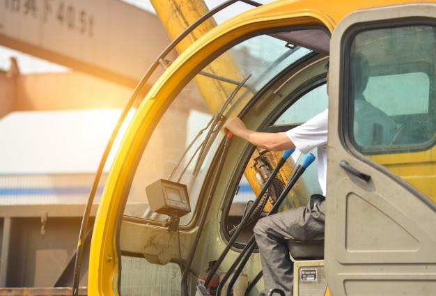 man-driving-crane-lift-up-some-equipments_1112-1222