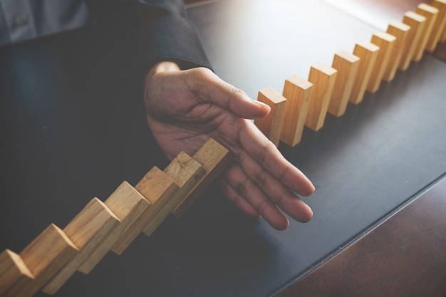 problem-solving-close-up-view-hand-business-woman-stopping-falling-blocks-table-concept-about-taking-responsibility_1418-55