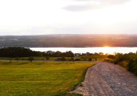 Photo of sunset with driveway in foreground and lake in background