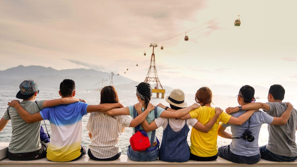 A group of people viewed from behind all with their arms around each other sitting on a ledge
