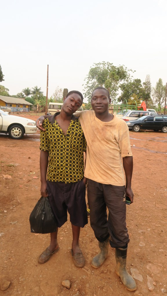 Two boys working at a car wash in Jinja Town