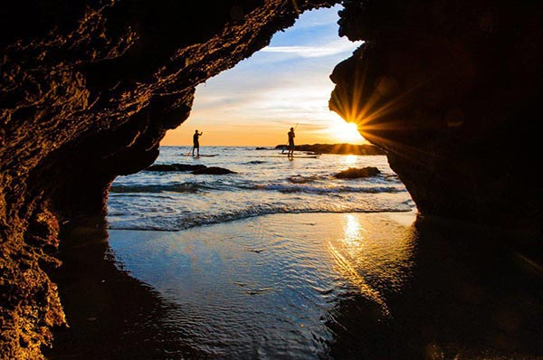 Standup Paddle sunset through cave